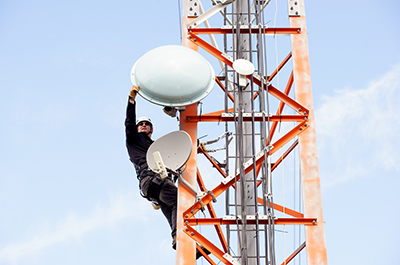 Ben Leslie of Columbia Wireless performs work on a tower overlooking Nelson. Photo credit: Colin Payne.