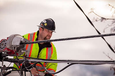 Contractors inspecting attachment of fibre optic cable to support cable on power poles. Photo credit: Colin Payne.